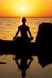 Yoga on sunset. Woman making yoga figure on the beach at sunset Stock Image
