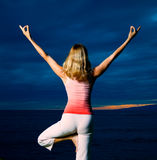 Yoga at Sunset. Woman Practicing Yoga in Front of Dramatic Sunset Royalty Free Stock Images