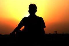 Yoga - sunset meditation. Young man meditating at sunset Royalty Free Stock Image