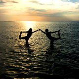 Yoga At Sunset. Yoga Poses at Sunset in the water Royalty Free Stock Photography