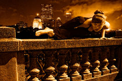 Yoga super hero on top of skyscraper. Female Yoga super hero doing arm balance on top of skyscraper cement balustrade, boston skyline is in the distance behind royalty free stock photo