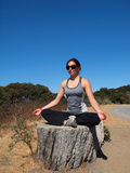 Yoga Superstar lady sits on tree stump, meditates Royalty Free Stock Image