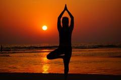Yoga sur la plage sur le coucher du soleil Photos stock