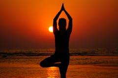 Yoga sur la plage sur le coucher du soleil Image stock