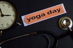 Yoga-Tag auf dem Druckpapier mit Gesundheitswesen-Konzept-Inspiration Wecker, schwarzes Stethoskop lizenzfreie stockbilder