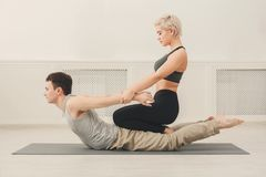 Young man with yoga instructor in fitness club. Yoga teacher and beginner in class, making asana exercises. Sporty men do back and shoulders stretching with Stock Image