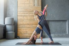 Young woman with yoga instructor in fitness club stock photos