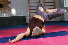 Yoga teacher in gymnasium. Yoga teacher demonstrates a complex exercise in gymnasium stock photos