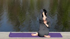 Yoga Teacher Make a Cow Pose Near Water. The Action in Real Time stock video footage