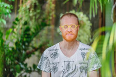 Yoga teacher portrait. Red hair man with a red beard. And yellow eyeglasses Stock Photos