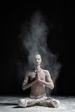A yoga teacher sits in a sukhasana on a black background. Dynamic kriyas against a background of white dust Stock Image
