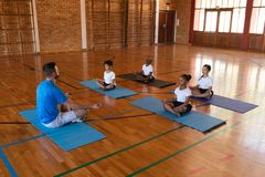 Yoga teacher teaching yoga to school kids in school. Side view of yoga teacher teaching yoga to school kids in school gymnast stock images