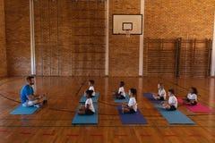 Yoga teacher teaching yoga to school kids in school. Side view of yoga teacher teaching yoga to school kids in school gymnast royalty free stock photo