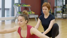 Yoga teacher in training helps to make a woman poses asanas for balance. Fitness instructor stands behind beginner student and teaches exercise with arms stock footage