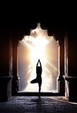 Yoga in temple. Yoga vrikshasana tree pose by man silhouette in old temple arch at dramatic sunset sky background. Free space for text Stock Photo