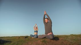 Yoga therapy, athletic woman and man together meditating in lotus position on mountain peak on background of blue sky. Yoga therapy, athletic woman and man stock video footage