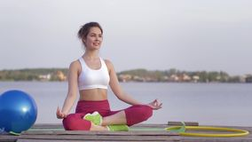 Yoga therapy, young beautiful yogi female in lotus position meditates and enjoys spiritual calmnes on nature. Near water stock video