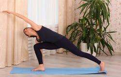 Yoga thuis De aantrekkelijke donkerbruine vrouw die yoga maakt thuis, ochtendtijd Gedraaide Zijhoek stelt Royalty-vrije Stock Foto's