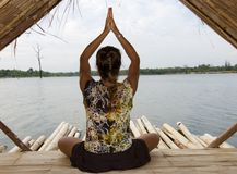 Yoga time. Woman in yoga position on bamboo mat at a lake Royalty Free Stock Photo