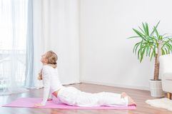 Beautiful woman is practicing yoga at home on yoga mat, doing Cobra exercise, Bhujangasana pose stock photography