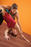 Yoga Trainer Assisting Student Stock Photo