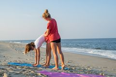Yoga class instructor helps beginner to make asana exercises. Woman doing yoga with trainer on the beach stock photography