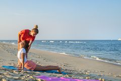 Yoga class instructor helps beginner to make asana exercises. Woman doing yoga with trainer on the beach royalty free stock photos