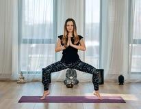 Yoga trainer executing asana Stock Photos