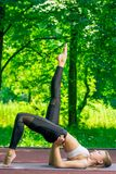 Yoga trainer performs simple outdoor exercise. In the park stock photography