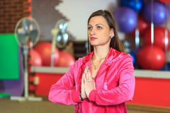 Yoga training. Beautiful white girl in a pink sports suit meditates on the yoga class at the fitness center. Royalty Free Stock Photography