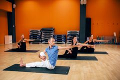 Yoga training class, female group workout. With male trainer in gym. Yogi exercise indoor Stock Image