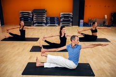Yoga training class, female group workout Royalty Free Stock Images