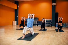 Yoga training class, female group workout stock photography