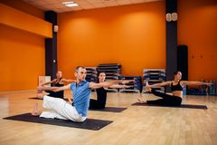 Yoga training, female group workout in gym Stock Photos