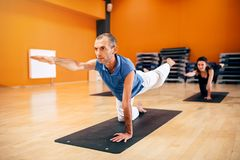 Yoga training group, fat burn exercise. Yoga training, female group with instructor, fat burn exercise, workout in gym. Yogi indoor Royalty Free Stock Photos