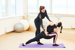Yoga training. Instructor controls of excercise execution. Yoga training. Instructor helps and controls of excercise execution royalty free stock image