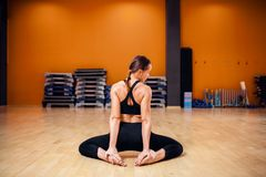 Yoga training, woman doing stretching exercise. Yoga training, woman in sportswear doing stretching exercise, back view, workout indoor. Yogi class in gym Stock Photo