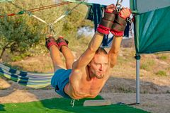Yoga treatment for core, yoga swing, slim young man strapped to four planks above the ground, man developing endurance. And stretching core royalty free stock photography