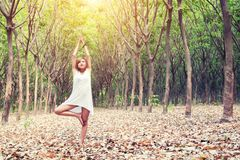 Yoga tree pose by beautiful young asian woman in white costume o. N green grass in the green forest Royalty Free Stock Photo