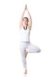 Yoga tree pose. Full length portrait of young fitness model in white sportswear doing yoga or pilates training, Vrikshasana, Tree Pose, studio shot, isolated Royalty Free Stock Images