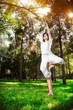 Yoga tree pose in the park. Yoga tree pose by woman in white costume on green grass in the park around pine trees Stock Photos