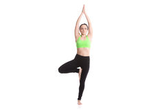 Yoga tree pose. Sporty girl on white background doing exercise for spine, standing in asana Vrikshasana (Vriksasana, Tree Pose), hands above the head in anjali Royalty Free Stock Photo