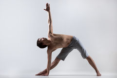 Yoga Triangle pose. Sporty muscular young man working out, yoga, pilates, fitness training, Triangle pose, Trikonasana, stretching exercise, gray background, low Stock Photos