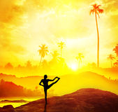 Yoga in tropical India. Man silhouette doing Yoga in tropics near the water at sunset in India Royalty Free Stock Photo