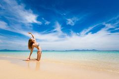 Yoga on tropical thai beach. Tropical summer yoga session on beautiful sunrise beach, Koh Kradan island in Thailand. camel pose, Ardha Ustrasana Royalty Free Stock Photo