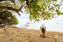 Yoga on tropical thai beach. Tropical summer yoga session on beautiful sunrise beach, Koh Kradan island in Thailand. Meditation - lotus pose - padma asana Stock Photos