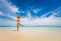 Yoga on tropical thai beach. Tropical summer yoga session on beautiful sunrise beach, Koh Kradan island in Thailand. Vriksha asana - tree pose Royalty Free Stock Images