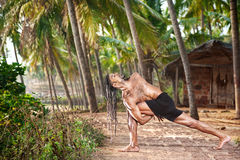 Yoga twisting pose. Yoga Baddha Parivrtta Parsvakonasana Revolved side angle pose by fit man with dreadlocks on the beach near the fishermen hut in Varkala Stock Images