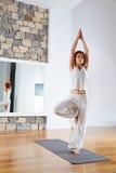Yoga una actitud del árbol de la balanza de la pierna en piso de madera Imágenes de archivo libres de regalías