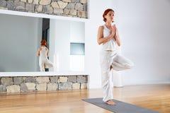 Yoga una actitud del árbol de la balanza de la pierna en piso de madera Foto de archivo